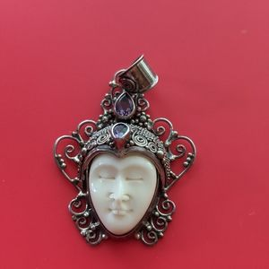 Pendant with moon face and purple stone in silver